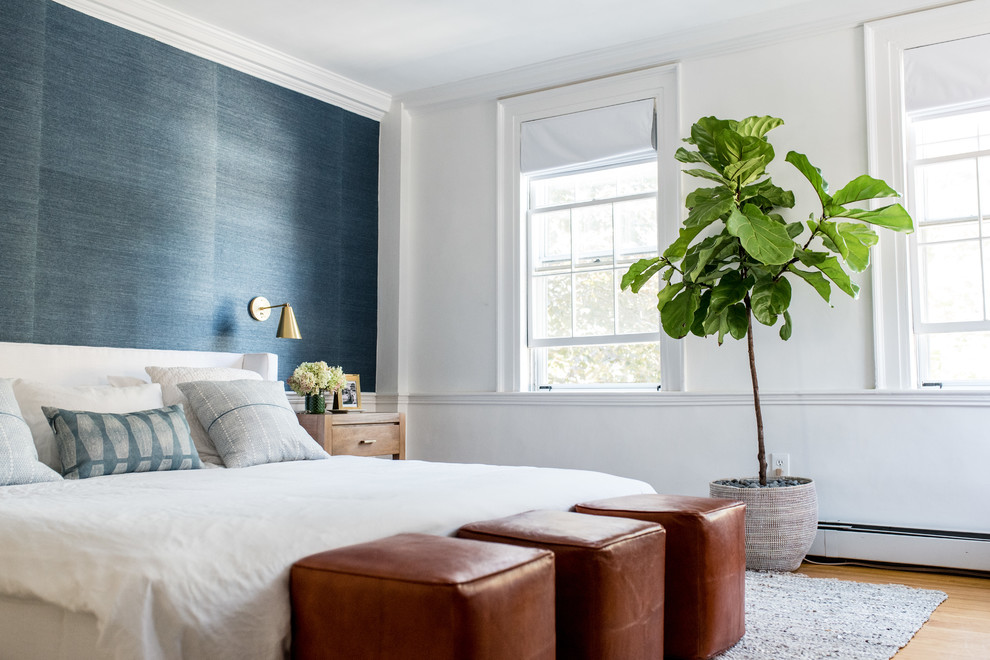 Example of a beach style master medium tone wood floor and brown floor bedroom design in Boston with white walls and a standard fireplace