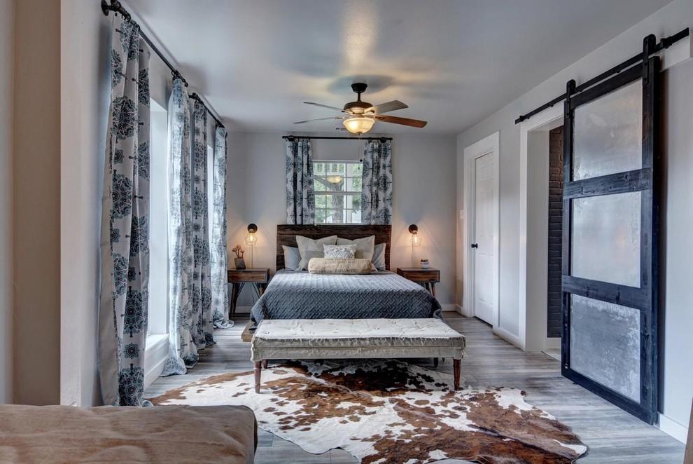 Bedroom - large farmhouse master medium tone wood floor and gray floor bedroom idea in Austin with gray walls