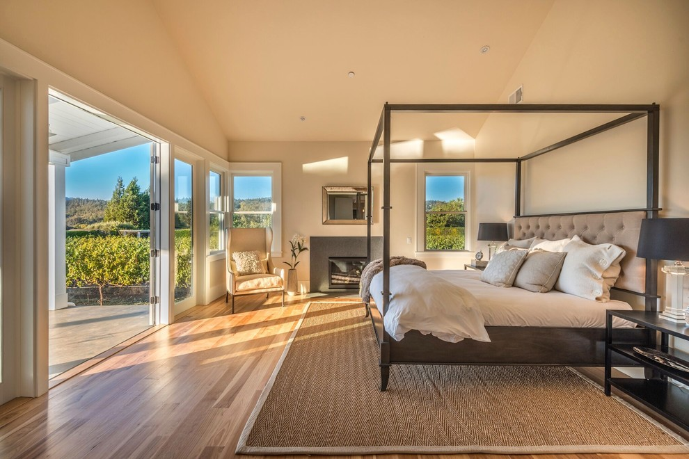 Inspiration for a cottage medium tone wood floor and brown floor bedroom remodel in San Francisco with beige walls and a standard fireplace