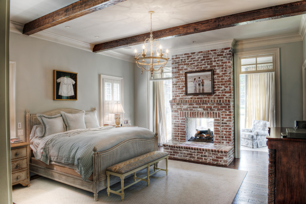 Inspiration for a mid-sized timeless master medium tone wood floor bedroom remodel in Other with gray walls, a brick fireplace and a two-sided fireplace