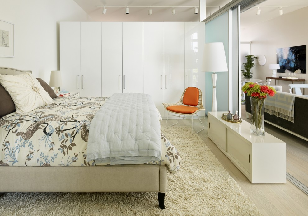 Urban light wood floor bedroom photo in Los Angeles with white walls