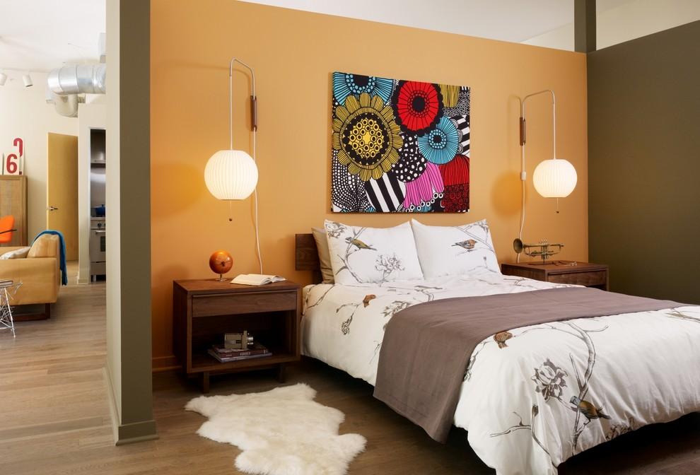 Inspiration for an industrial medium tone wood floor bedroom remodel in Los Angeles with orange walls