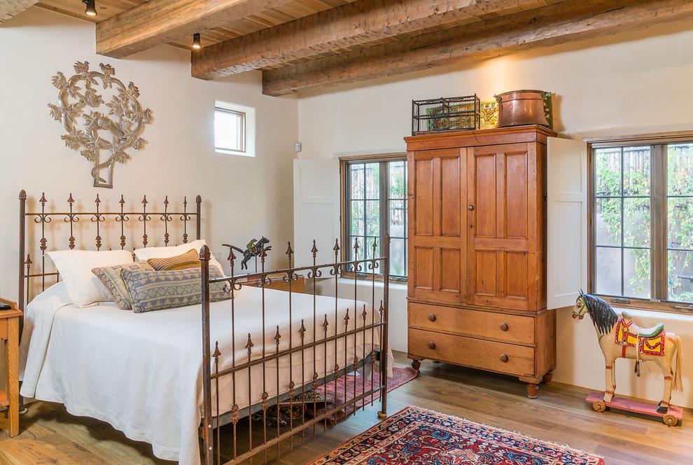 Southwest dark wood floor and brown floor bedroom photo in Albuquerque with white walls