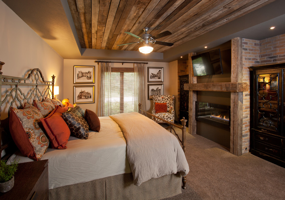 Bedroom - mid-sized rustic master carpeted and beige floor bedroom idea in Other with beige walls, a ribbon fireplace and a wood fireplace surround