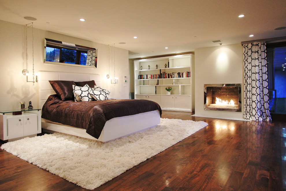 Trendy dark wood floor bedroom photo in Los Angeles with white walls and a standard fireplace