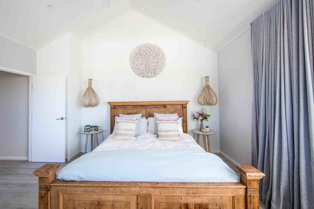 Design ideas for a mid-sized beach style master bedroom in Gold Coast - Tweed with white walls, painted wood floors and grey floor.
