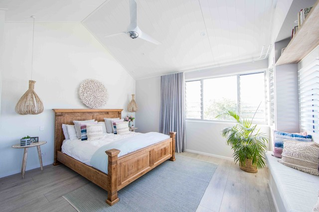 Photo of a mid-sized beach style master bedroom in Gold Coast - Tweed with white walls, painted wood floors and grey floor.