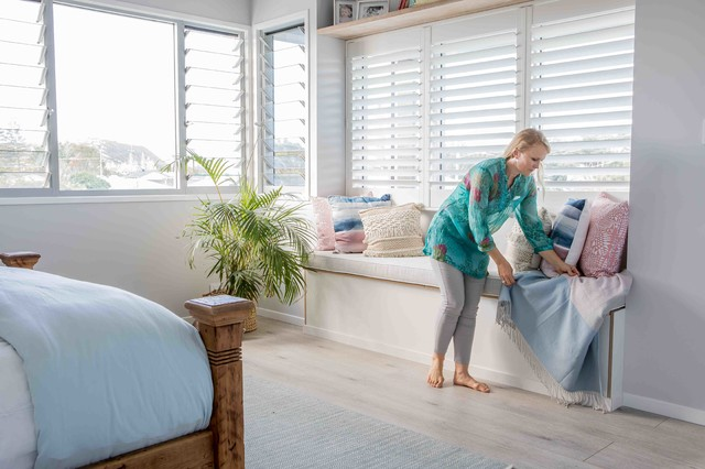 Inspiration for a mid-sized beach style master bedroom in Gold Coast - Tweed with white walls, painted wood floors and grey floor.