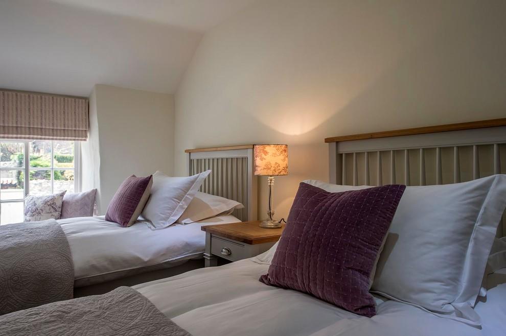 Foto de habitación de invitados campestre, de tamaño medio, con paredes beige, moqueta, todas las chimeneas, marco de chimenea de piedra y suelo beige