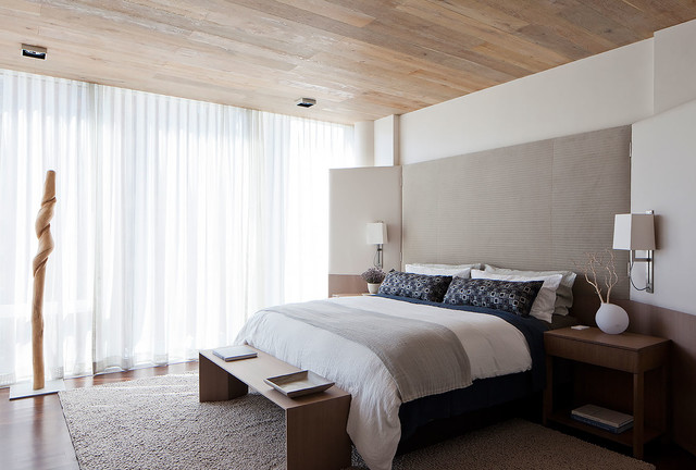 Inspiration for a contemporary master medium tone wood floor bedroom remodel in New York with white walls