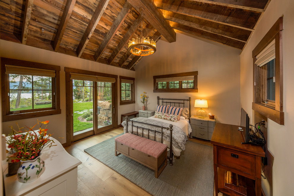 Example of a mid-sized mountain style guest light wood floor and beige floor bedroom design in Denver with beige walls and no fireplace