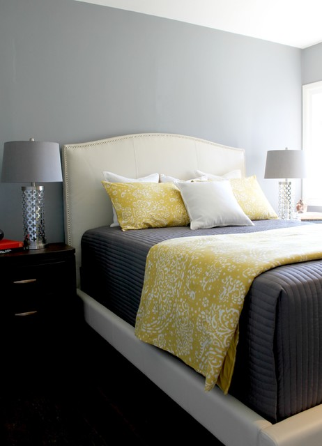 gray yellow and white bedding on a white upholstered bed