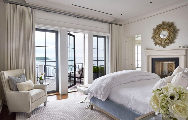 Inspiration for a timeless medium tone wood floor and brown floor bedroom remodel in Vancouver with white walls and a standard fireplace