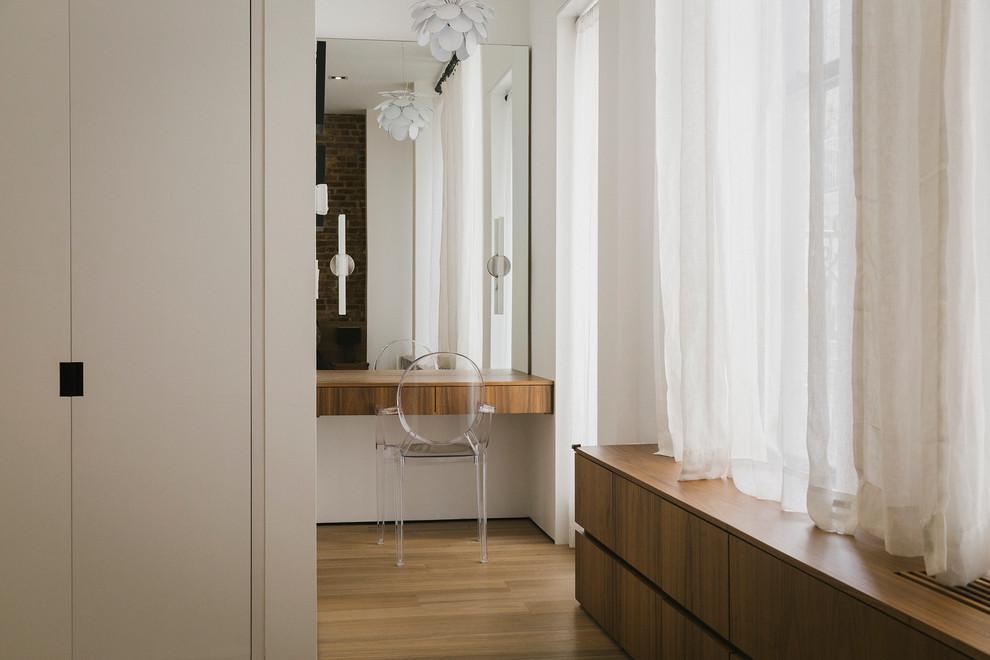 Foto de dormitorio principal, actual, sin chimenea, con suelo de madera en tonos medios y paredes blancas
