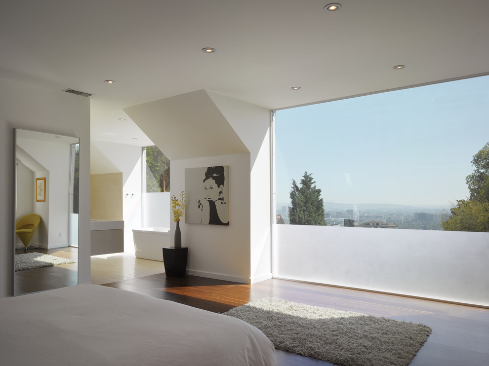 Example of a small minimalist master dark wood floor bedroom design in Los Angeles with white walls and no fireplace