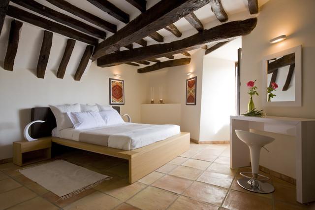 Bedroom - mediterranean terra-cotta floor and orange floor bedroom idea in Marseille with beige walls