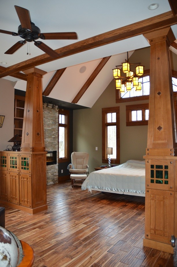 Example of a large mountain style master light wood floor bedroom design in Indianapolis with green walls, a standard fireplace and a stone fireplace