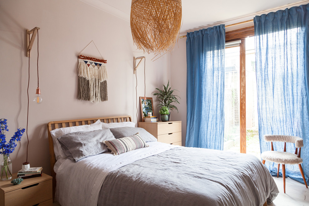 Example of a mid-sized eclectic master painted wood floor and white floor bedroom design in London with pink walls