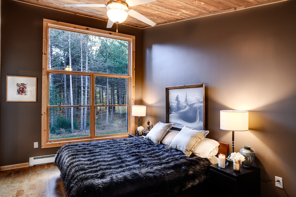Example of a mid-sized mountain style master bamboo floor and brown floor bedroom design in New York with no fireplace and gray walls