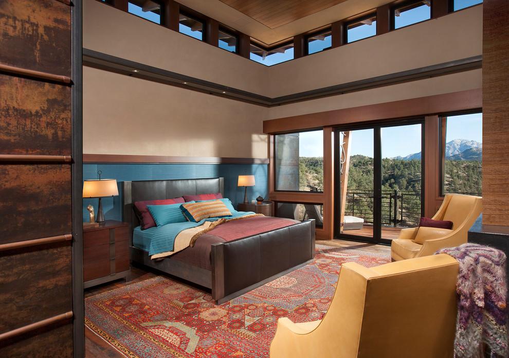 Example of a large southwest master brown floor and dark wood floor bedroom design in Phoenix with beige walls