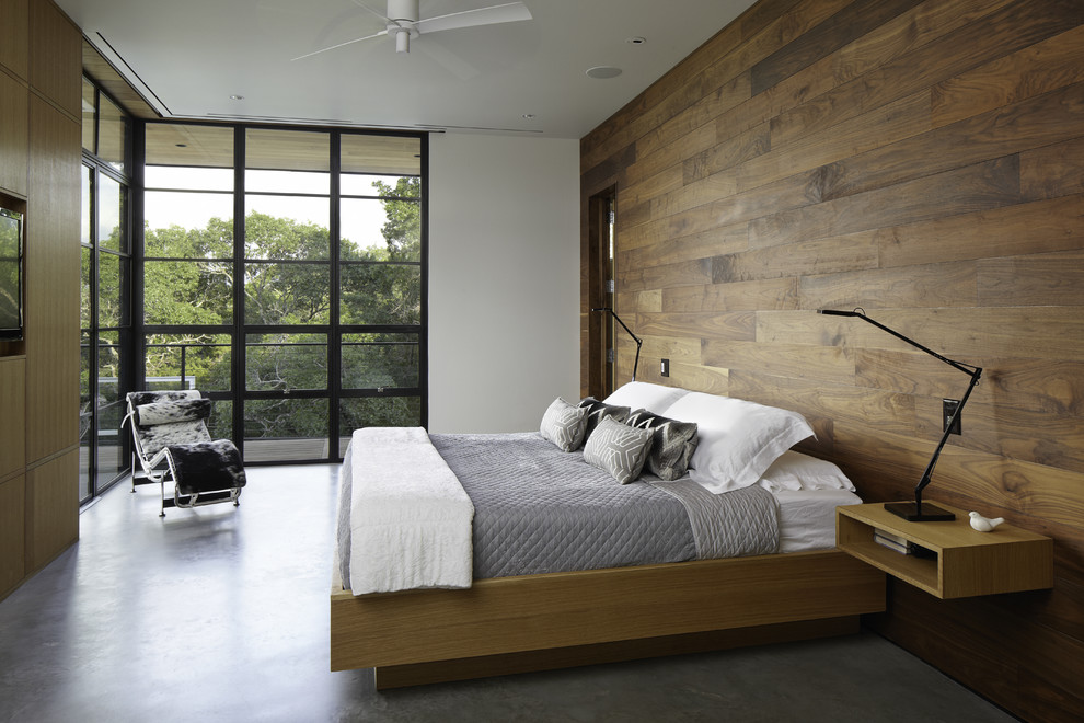 Example of a minimalist concrete floor and gray floor bedroom design in Austin