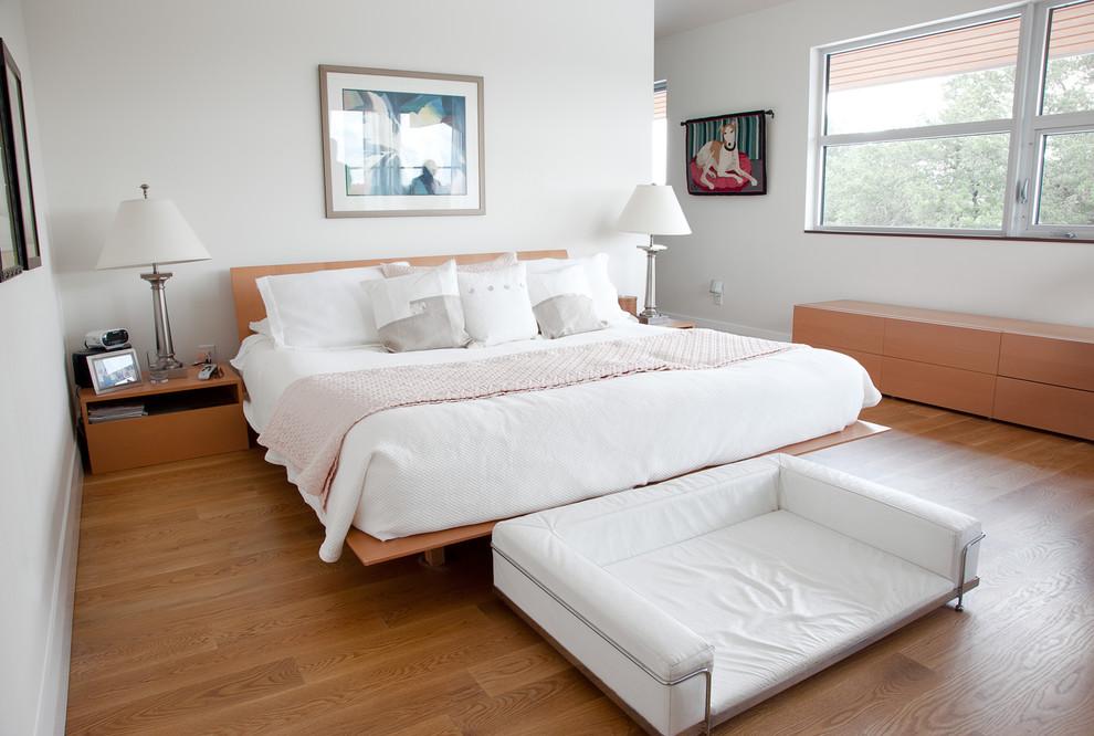 Example of a minimalist medium tone wood floor bedroom design in Austin with white walls
