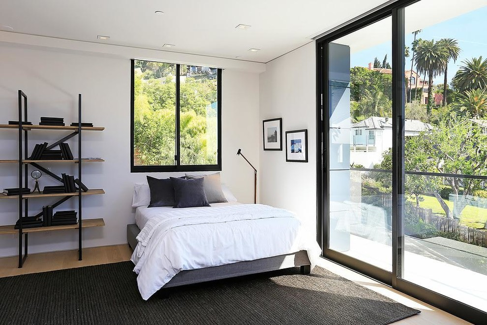 Example of a mid-sized trendy guest light wood floor and beige floor bedroom design in Los Angeles with white walls and no fireplace