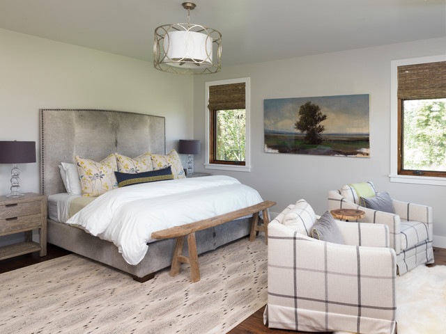 Inspiration for a mid-sized rustic master medium tone wood floor bedroom remodel in Other with beige walls and no fireplace