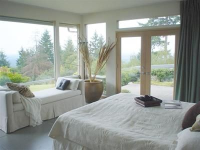 Natural light pours through large windows in this master bedroom.