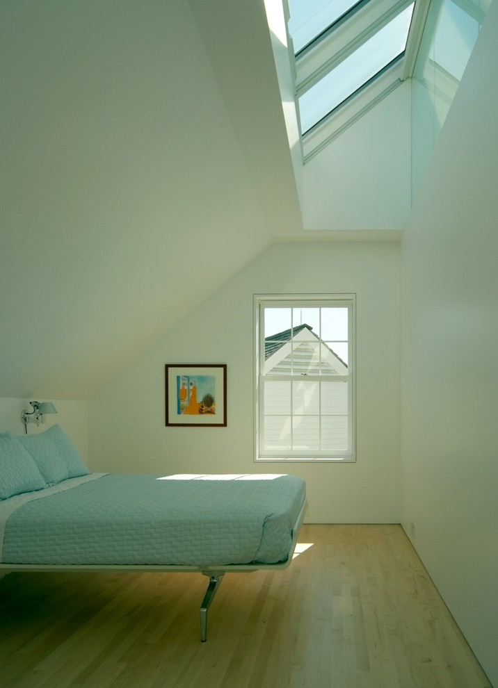 Example of a trendy medium tone wood floor bedroom design in Portland Maine with white walls