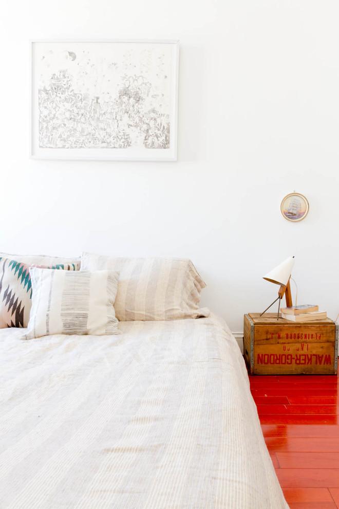 Bedroom - eclectic red floor bedroom idea in New York with white walls