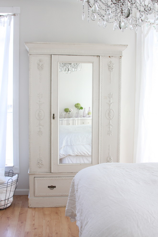 Cottage chic light wood floor bedroom photo in Other with white walls