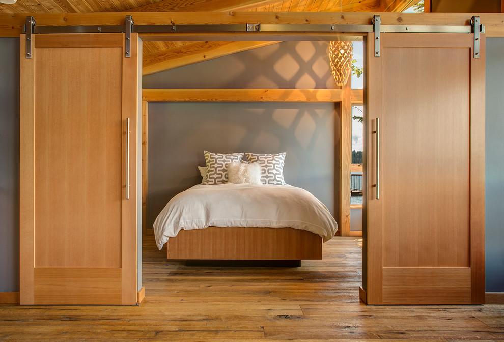 Trendy guest medium tone wood floor bedroom photo in Seattle with gray walls