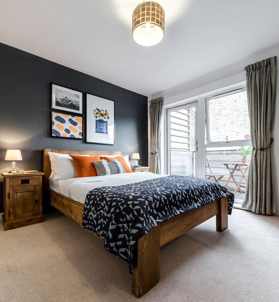 This is an example of a rustic bedroom in London with black walls and carpet.