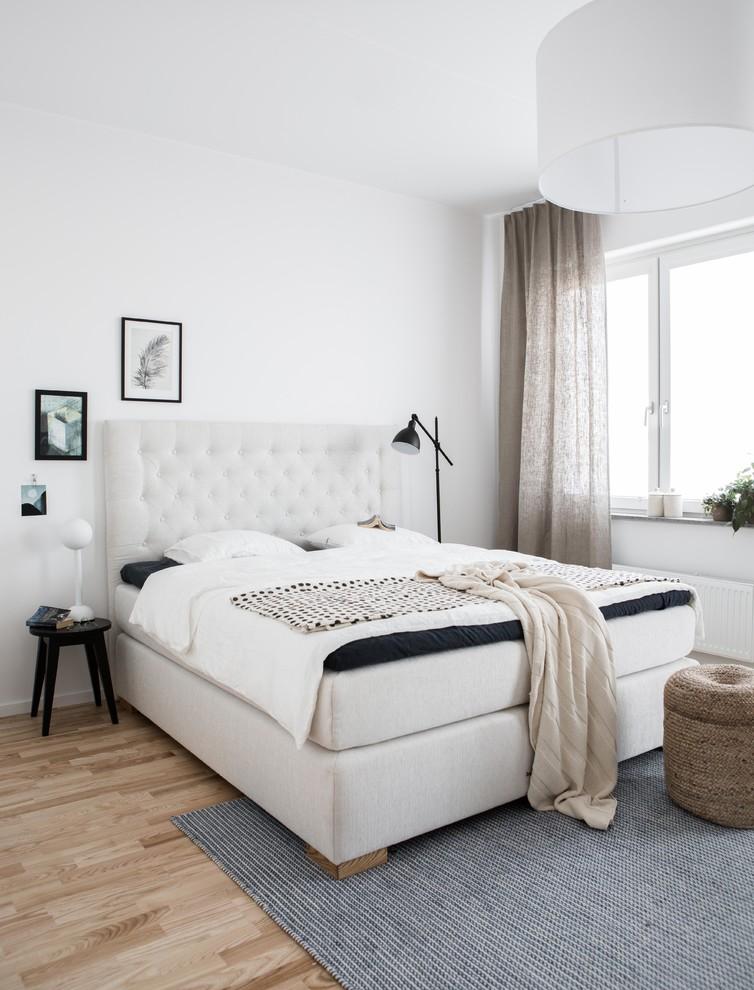Inspiration pour une chambre adulte nordique de taille moyenne avec un mur blanc, un sol en bois clair et aucune cheminée.