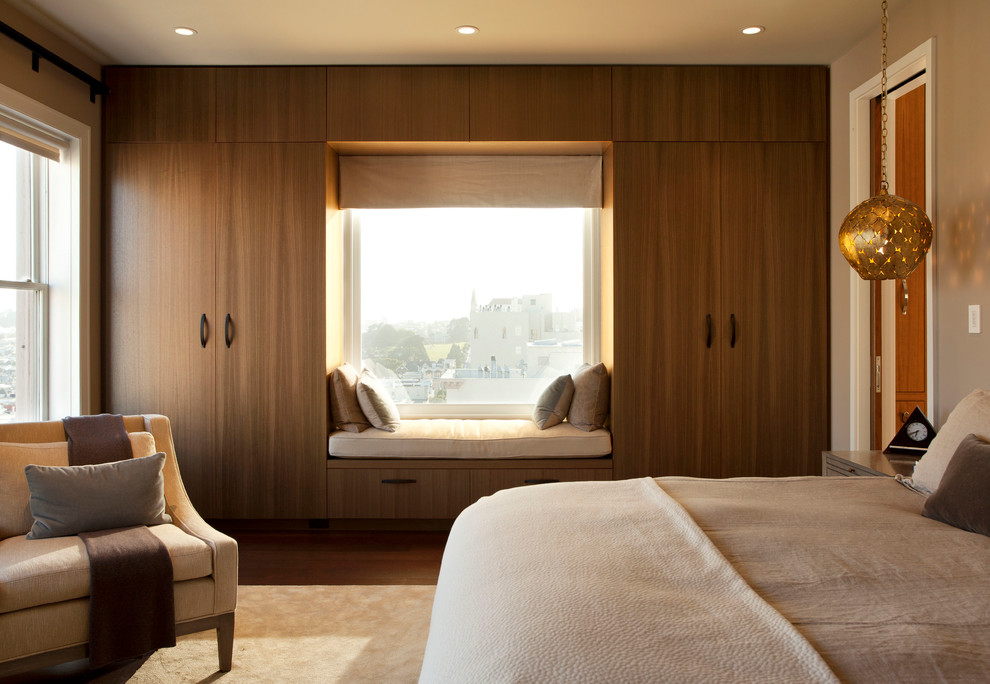 Large contemporary master bedroom in San Francisco with beige walls and dark hardwood flooring.