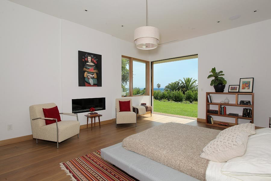 Large 1950s master medium tone wood floor bedroom photo in Los Angeles with white walls and a ribbon fireplace