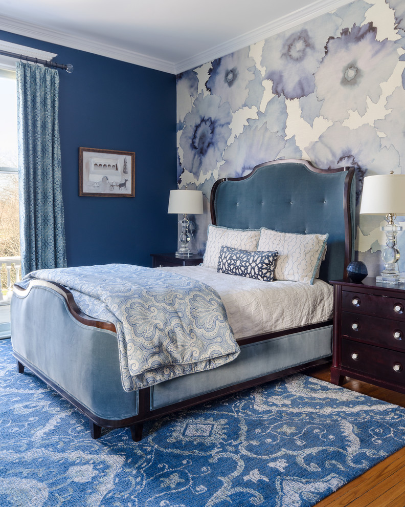 Elegant medium tone wood floor and brown floor bedroom photo in Richmond with blue walls