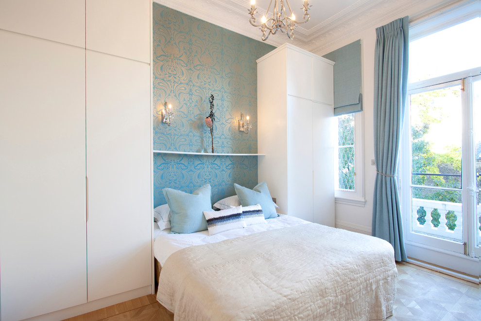 Example of a danish bedroom design in London with blue walls
