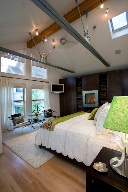 Example of a large urban master light wood floor and brown floor bedroom design in Salt Lake City with white walls and no fireplace