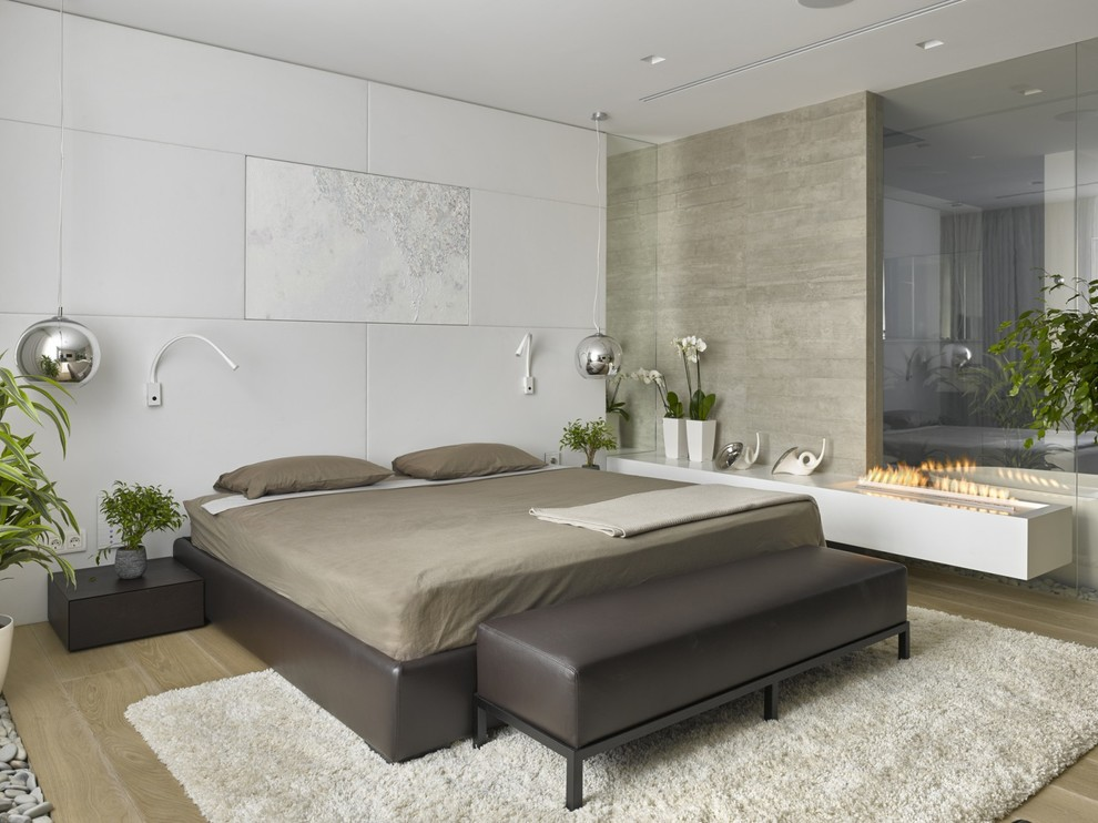 Inspiration for a mid-sized contemporary master light wood floor bedroom remodel in Moscow with white walls and a ribbon fireplace