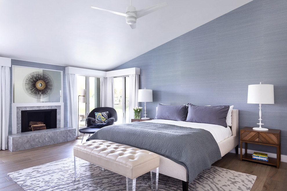 Example of a transitional master light wood floor bedroom design in Los Angeles with purple walls and a standard fireplace