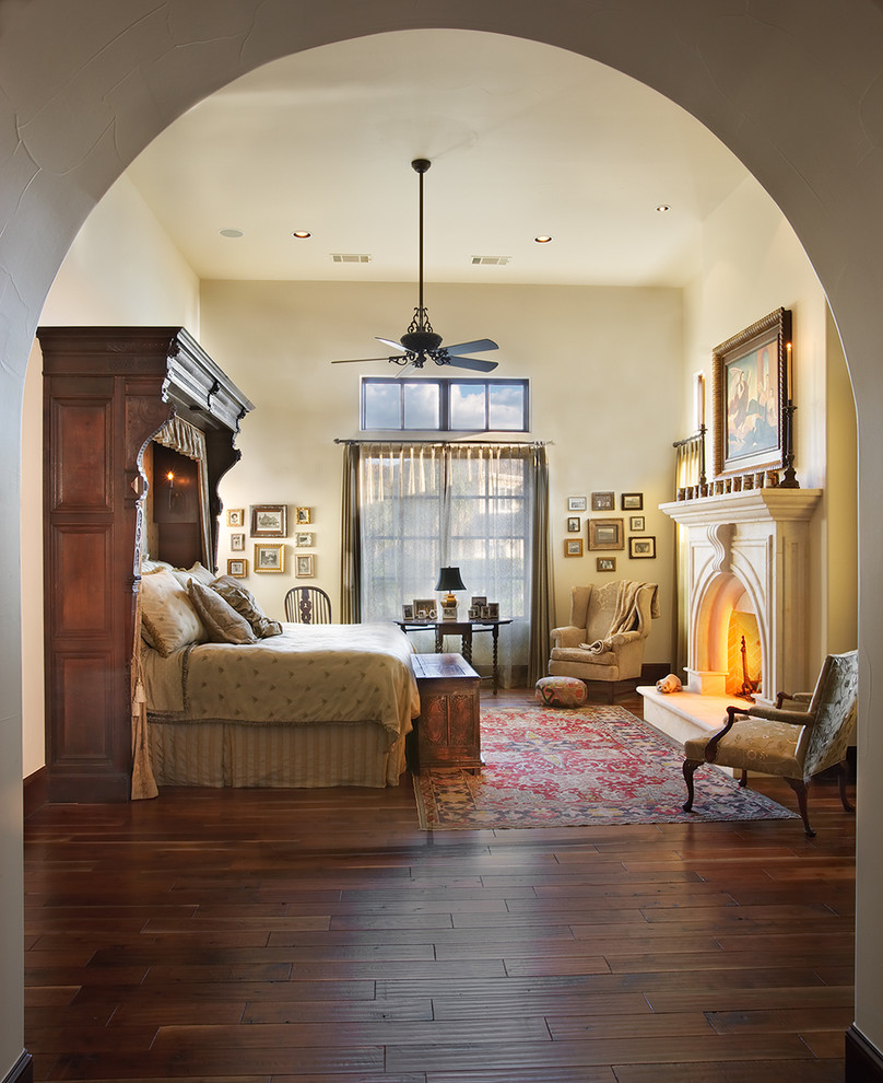 Tuscan master dark wood floor bedroom photo in Austin with beige walls, a standard fireplace and a stone fireplace