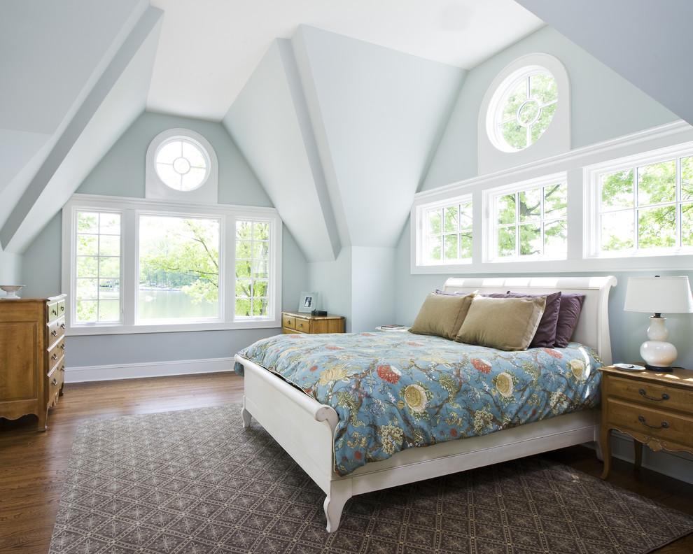 Elegant medium tone wood floor bedroom photo in New York with blue walls