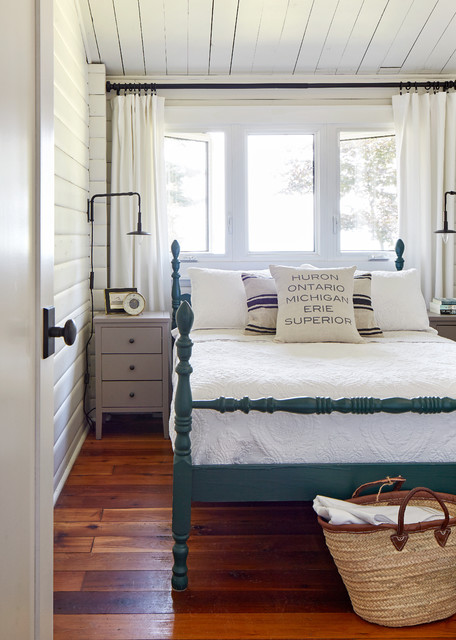 Inspiration for a mid-sized beach style guest medium tone wood floor and brown floor bedroom remodel in Toronto with white walls
