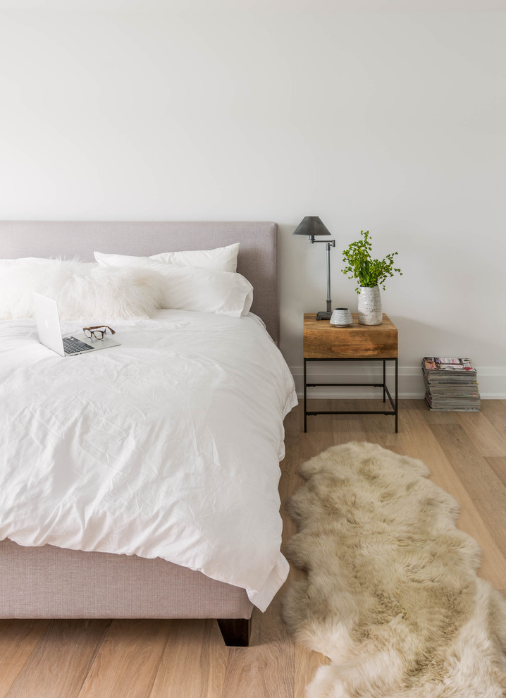 Example of a danish light wood floor bedroom design in Toronto with white walls