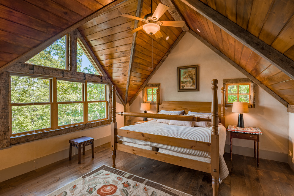 Example of a mid-sized mountain style medium tone wood floor bedroom design in Other with beige walls