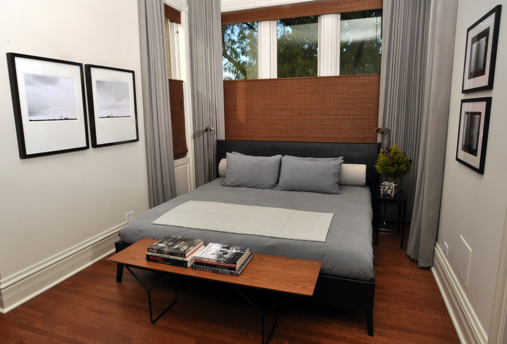 Example of a large trendy master medium tone wood floor bedroom design in Chicago with white walls