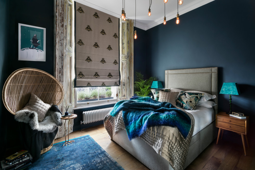 Bedroom - eclectic master medium tone wood floor bedroom idea in London with blue walls and no fireplace