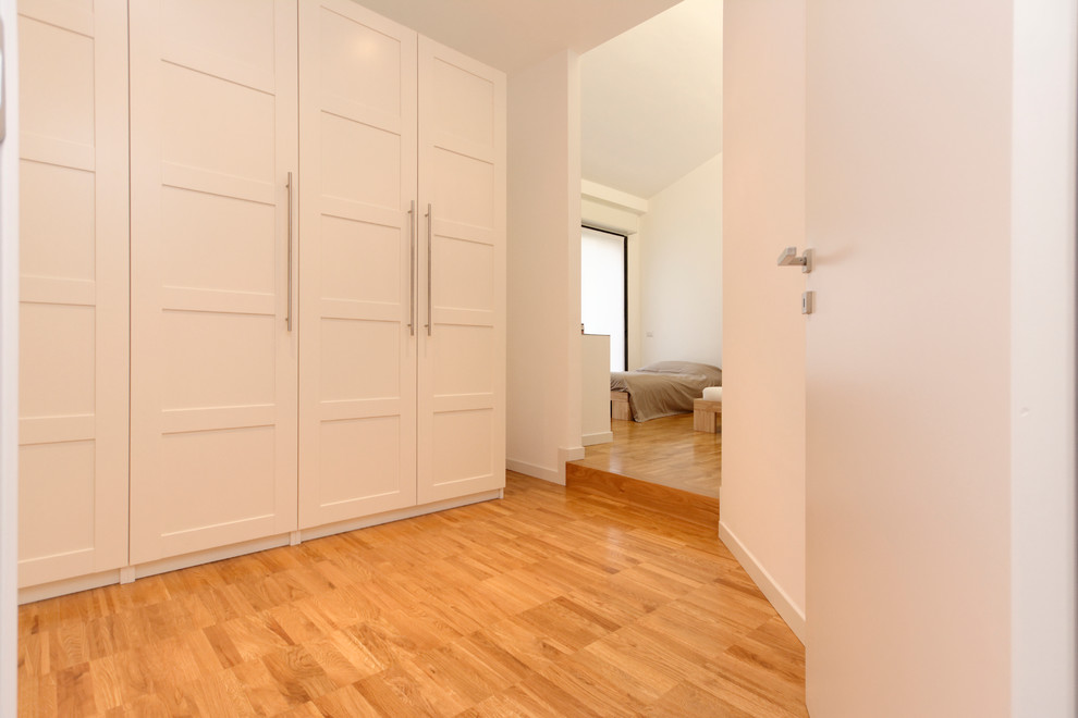 Example of a mid-sized trendy light wood floor bedroom design in Milan with white walls and no fireplace